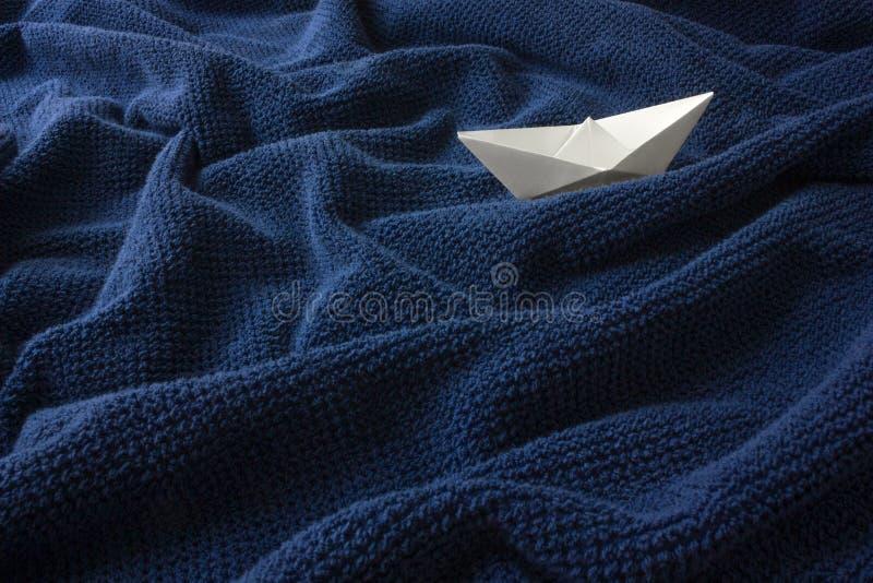 Papierowa łódź na błękitnej falistej bawełnianej tkaninie obraz stock