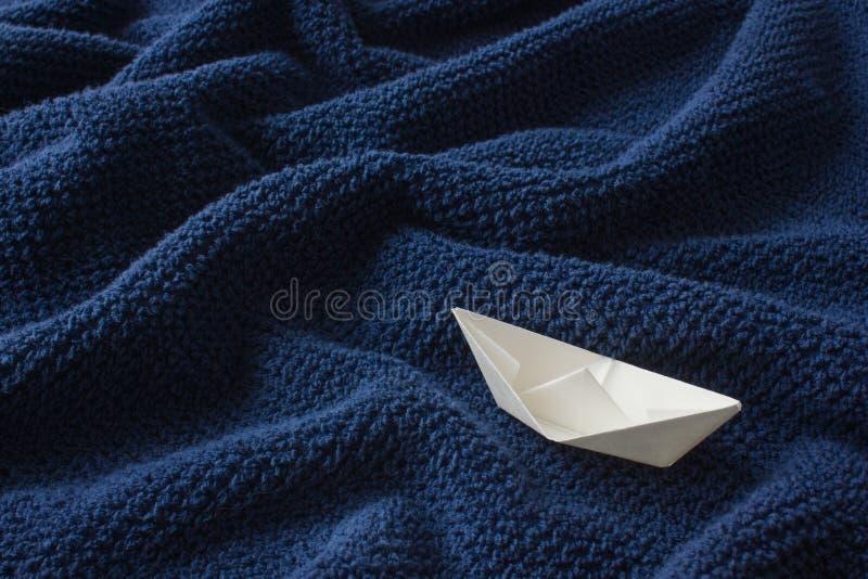 Papierowa łódź na błękitnej falistej bawełnianej tkaninie zdjęcia stock