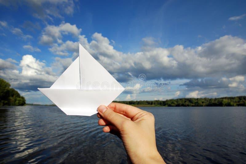 Papierowa żaglówka w ręce przeciw pięknemu rzeka krajobrazowi Niebieskie niebo, chmury fotografia stock