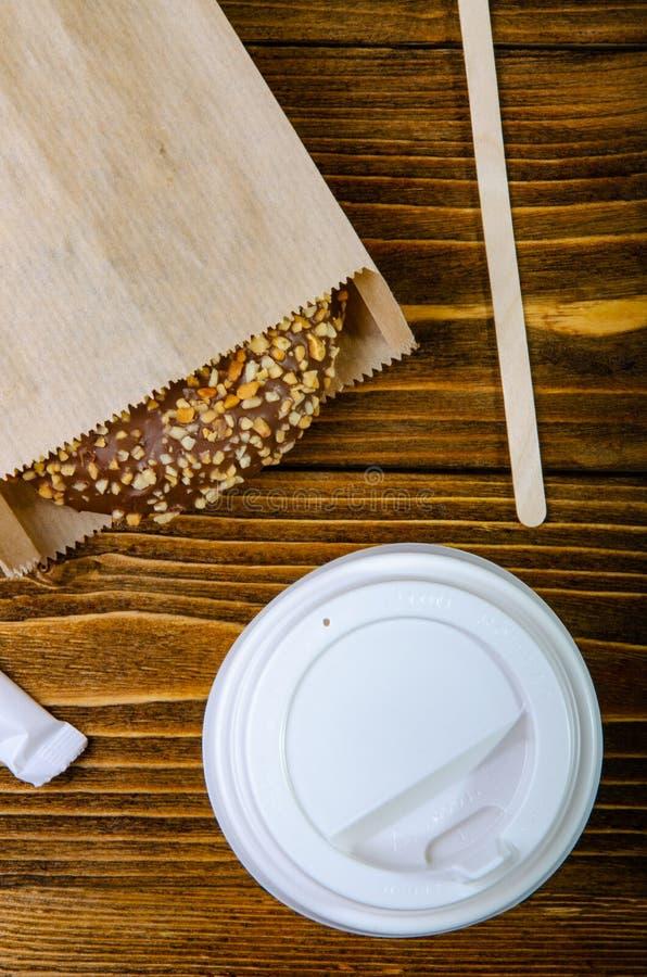 Papierowa filiżanka dla kawy, rozporządzalne ekologiczne kaw dostawy Donuts na papierowych tacach tabela drewna fotografia royalty free