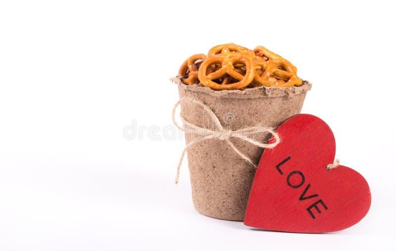 Papierowa filiżanka z słonymi krakers i czerwonym drewnianym sercem na białym tle obraz stock