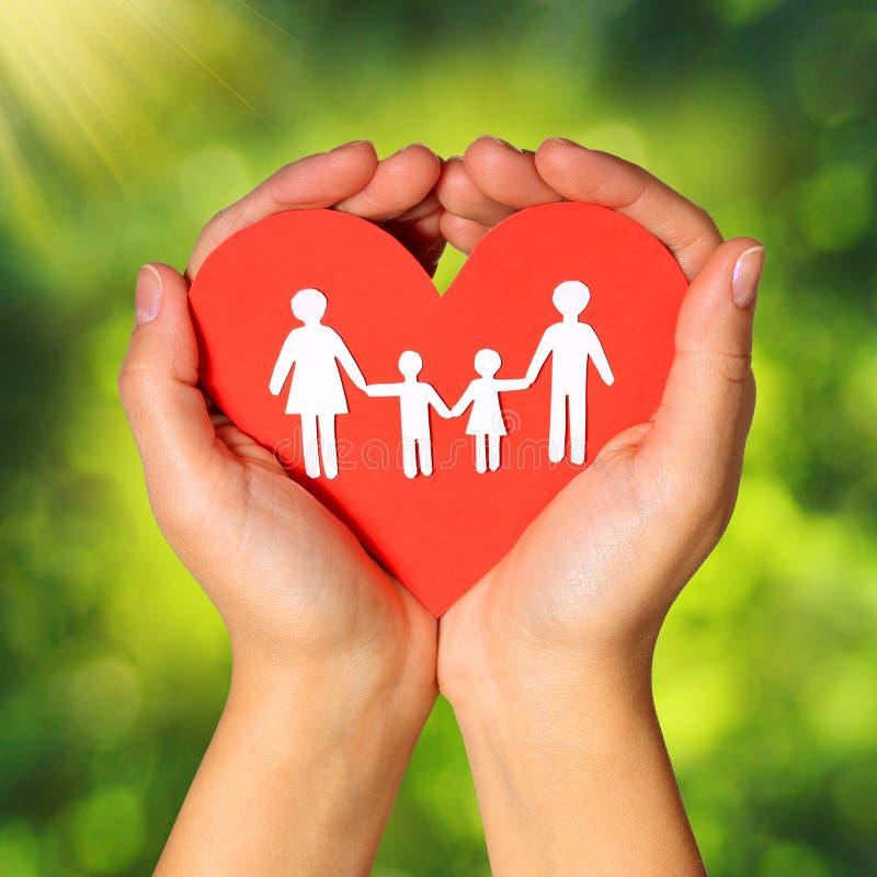Papierowa rodzina i serce w rękach nad Zielonym Pogodnym tłem fotografia stock