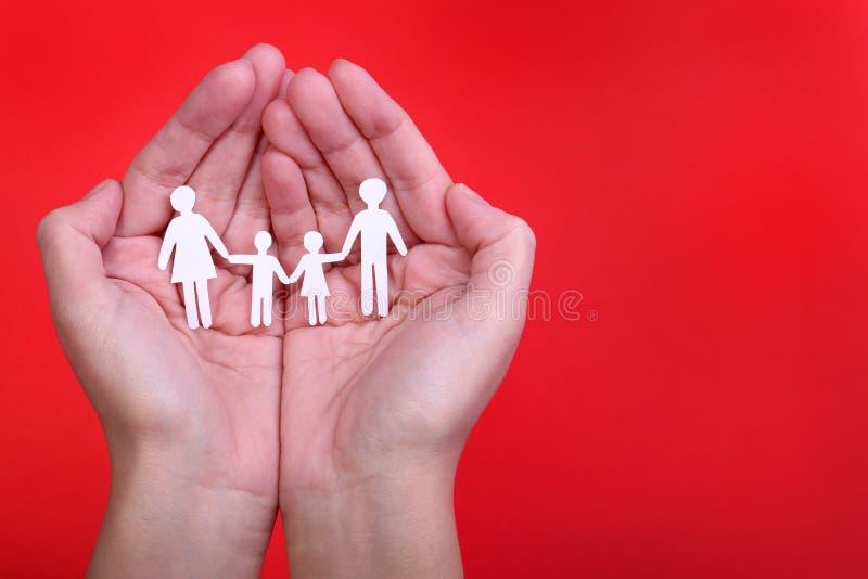 Papierowa rodzina w rękach nad czerwonym tłem. Rodzina i dzieciaki zdjęcia royalty free