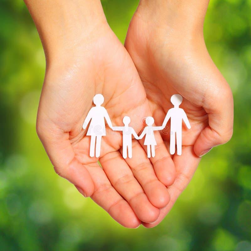Papierowa rodzina w rękach nad Zielonym Pogodnym tłem. Rodzina obraz stock