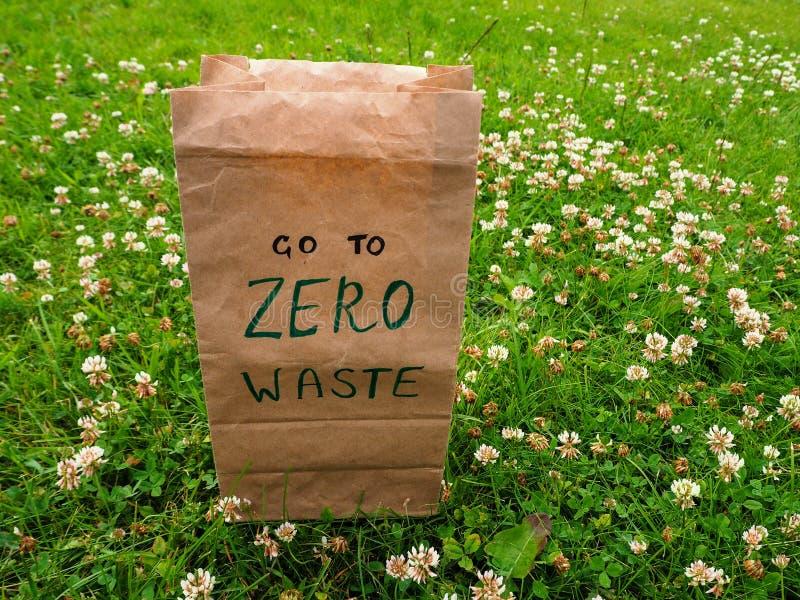 Papierowa torba z ręcznie pisany słowami Iść zero odpadów na nim «stoi wśród koniczynowej i zielonej trawy obrazy stock