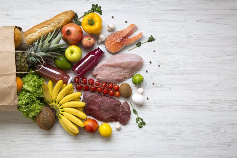 Papierowa torba zdrowy surowy jedzenie na białym drewnianym stole Kulinarny karmowy tło Lay świeże owoc, veggies, zielenie, różne zdjęcie royalty free