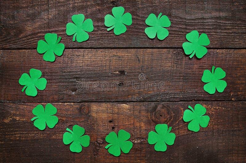 Papierowa zielona koniczynowa shamrock liścia granicy rama na ciemnym drewnianym tle zdjęcia stock