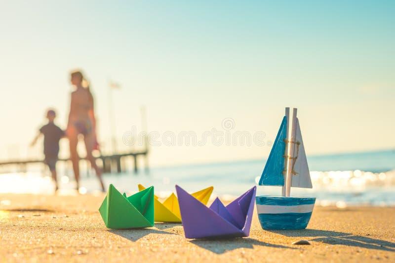 Papierowe łodzie, drewniana łódź i odprowadzeń ludzie przy plażą, zdjęcie royalty free