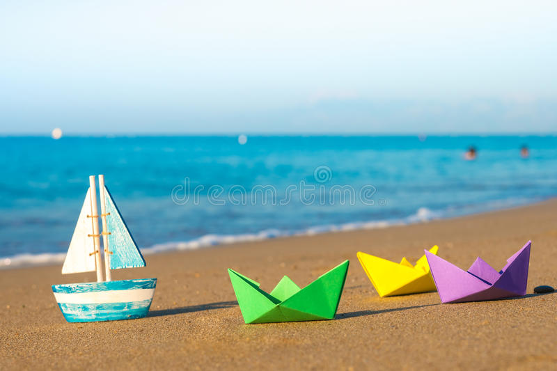 Papierowe łodzie i drewniana łódź przy seashore fotografia royalty free