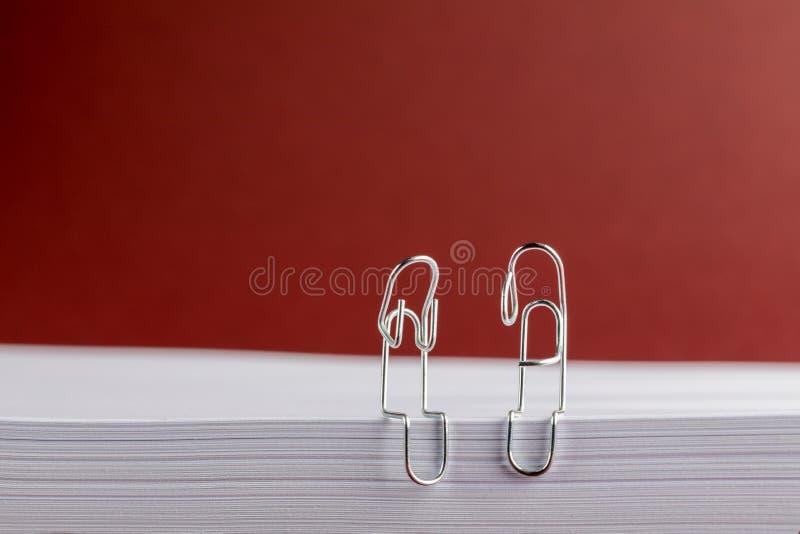 Papierowe klamerki na Czerwonym tle Patrzeje Smutny zdjęcia stock