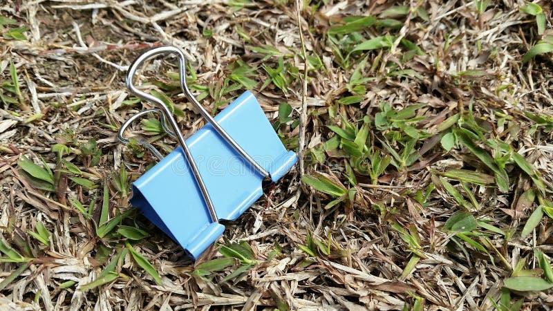 Papierowej klamerki błękit na trawa właścicielu obrazy stock