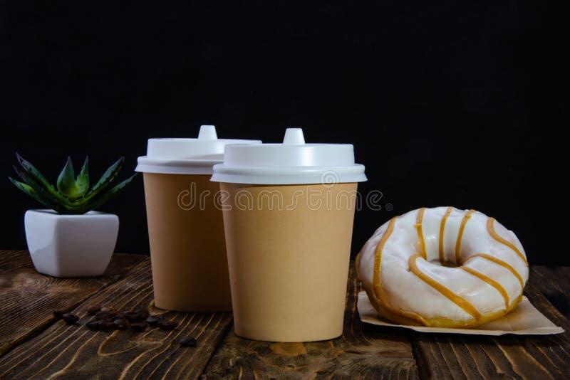 Papierowi fili?anka kawy, cukier w torbach, donuts tabela drewna Czarny t?o zdjęcia stock