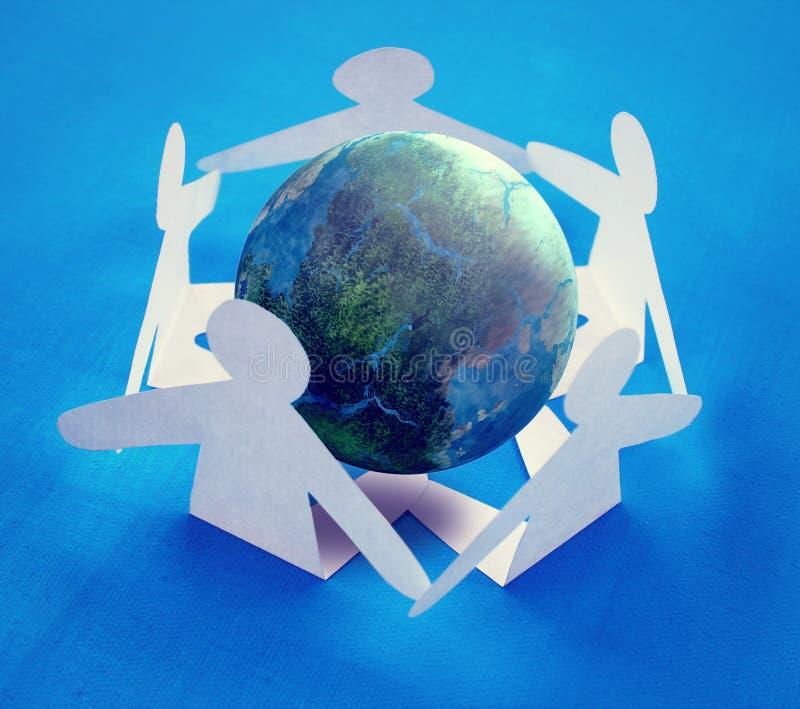Papierowi ludzie siedzi wokoło kuli ziemskiej zdjęcie royalty free