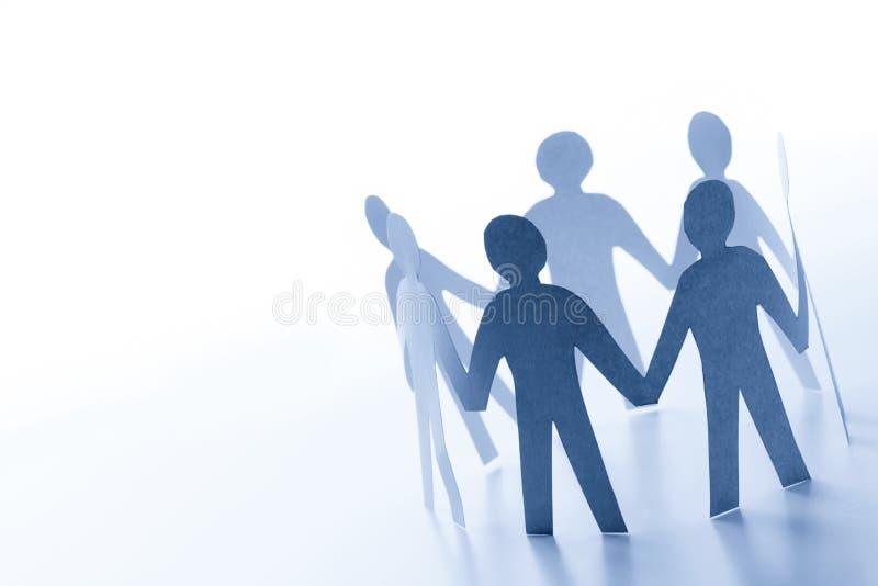 Papierowi ludzie stoi wpólnie ręka w rękę drużyna zdjęcie stock