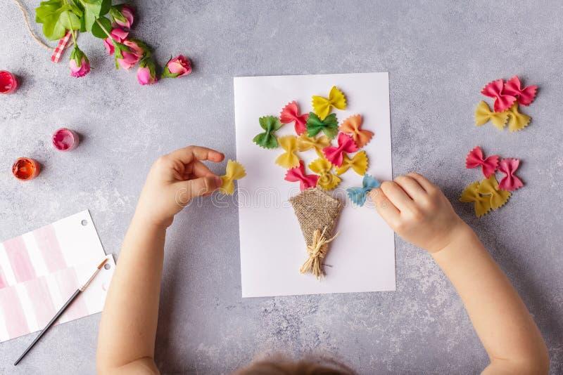 Papierowi rzemiosła dla macierzystego dnia, 8 maszerują lub urodziny Mały dziecko robi bukietowi kwiaty z barwionego papieru i ba obrazy royalty free