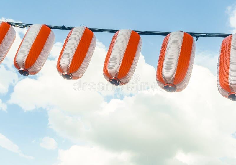 Papierowy biały japońskich lampionów Chochin obwieszenie na niebieskiego nieba tle zdjęcie stock