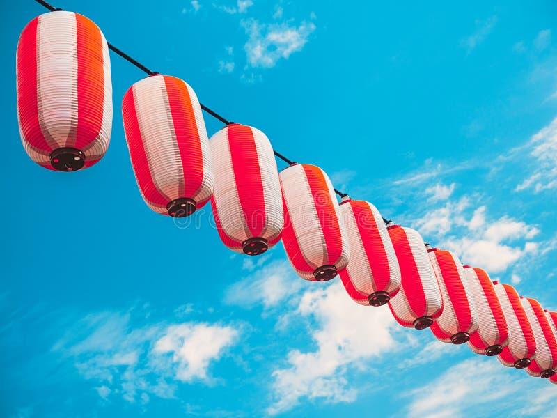 Papierowy biały japońskich lampionów Chochin obwieszenie na niebieskiego nieba tle zdjęcia stock