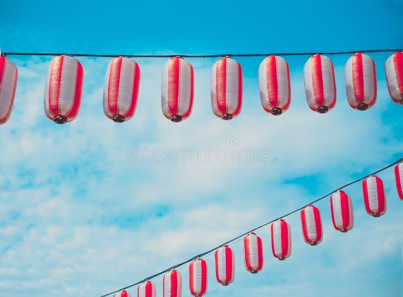 Papierowy biały japońskich lampionów Chochin obwieszenie na niebieskiego nieba tle obrazy royalty free