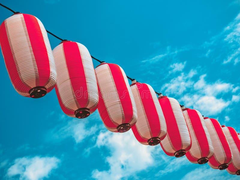Papierowy biały japońskich lampionów Chochin obwieszenie na niebieskiego nieba tle fotografia stock