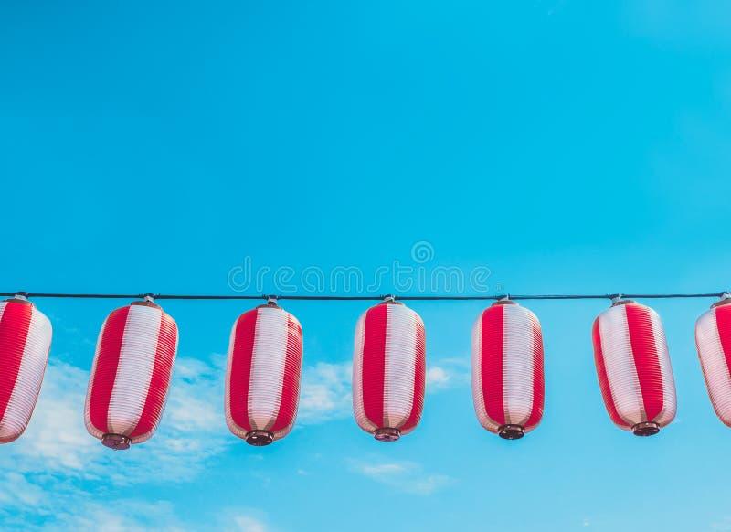 Papierowy biały japońskich lampionów Chochin obwieszenie na niebieskiego nieba tle obraz royalty free