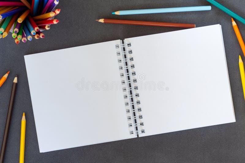 Papierowy notatnik, pusta biała księga i barwioni ołówki na ciemnego tła odgórnym widoku, obraz stock