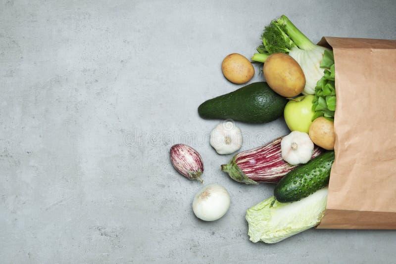 Papierowy pakunek z świeżymi warzywami i owoc na koloru tle, mieszkanie nieatutowy zdjęcie royalty free