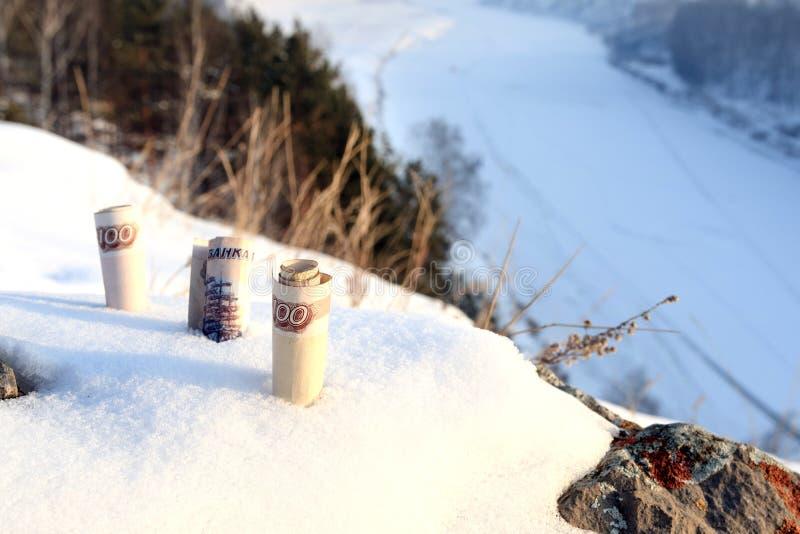 Papierowy pieniądze wtykał w śniegu w tle śnieżni lasy i rzeki pod lodem obrazy stock