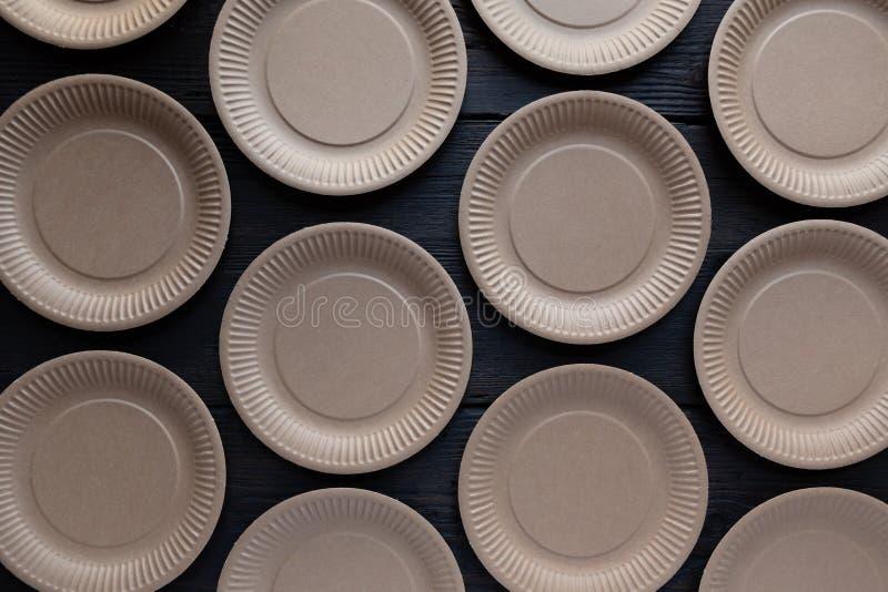 Papierowy rozporządzalny talerza wzór na ciemnym drewnianym tle Lata przyjęcie, kuchenny cutlery zdjęcie stock