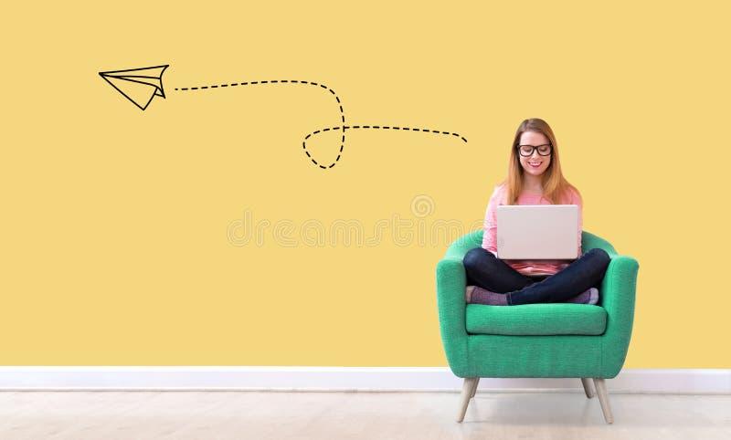 Papierowy samolot z kobietą używa laptop zdjęcia stock