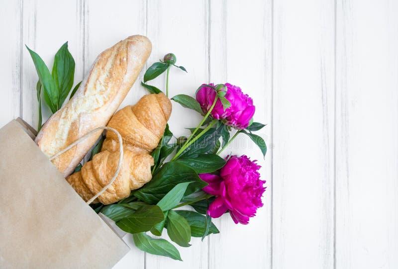 Papierowy torba na zakupy z świeżym chlebem, croissants i peonią, kwitnie Mieszkanie nieatutowy, odgórny widok obrazy royalty free