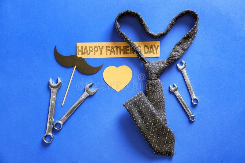 """Papierowy wąsy, narzędzia, krawat i etykietka, z, na koloru tle tekstem, Szczęśliwym ojcem, «s dniem"""" """"« zdjęcia royalty free"""