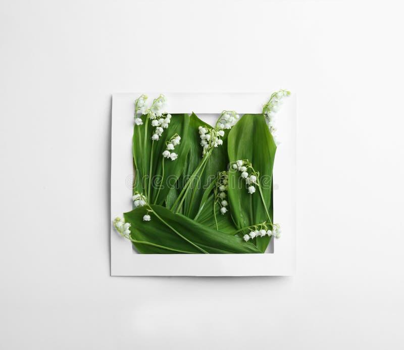 Papierrahmen mit Maiglöckchenblumen auf weißem Hintergrund stockfotos