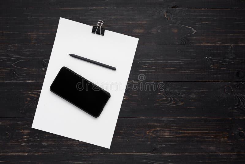 Papiers avec le stylo et cellulaire sur le fond en bois photo stock
