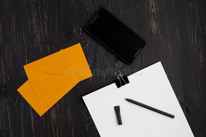Papiers avec le stylo et les enveloppes et cellulaire sur le fond en bois photographie stock