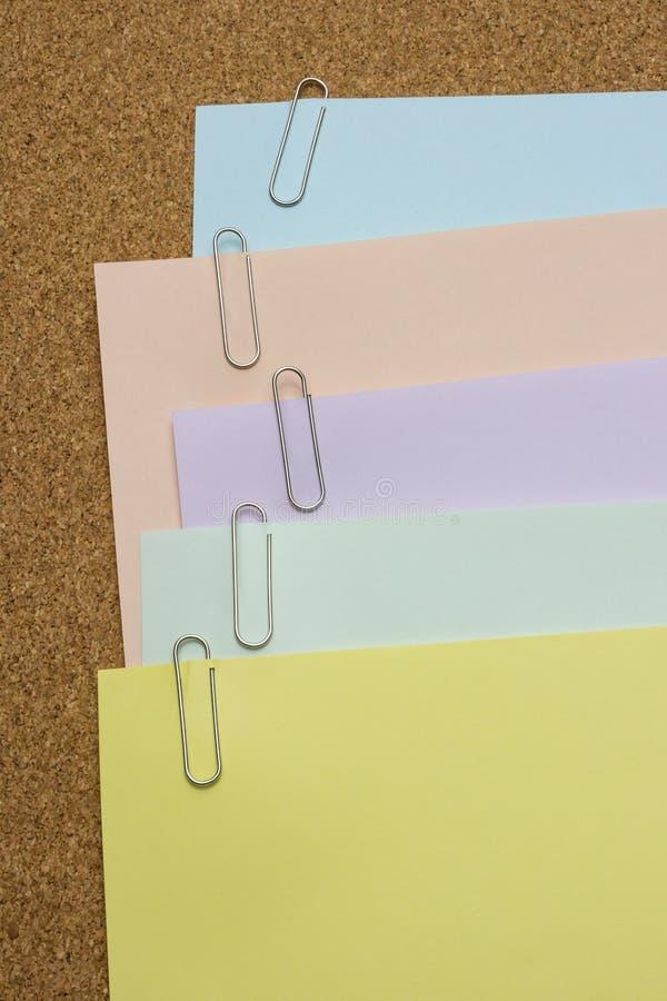 Papiers avec le trombone attaché sur le conseil brun photographie stock libre de droits