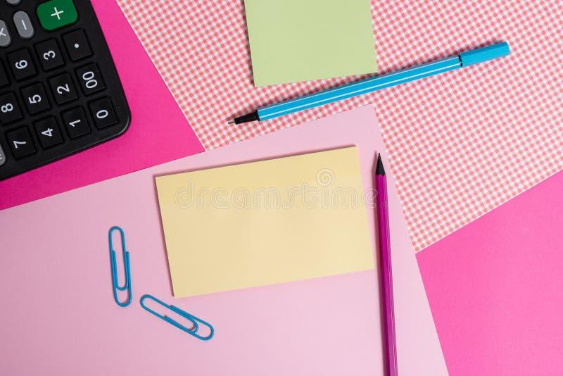 Papiers stationnaires et de notation placés au-dessus du contexte coloré Inscription des équipements avec des feuilles de note su images libres de droits