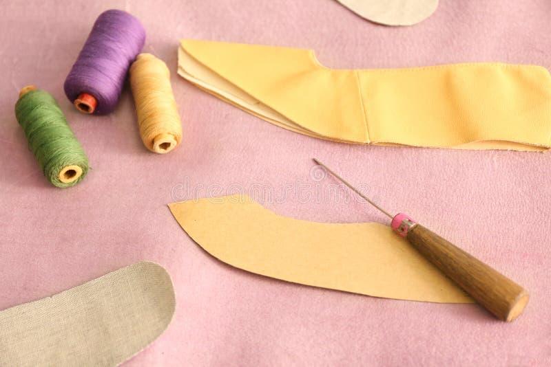 Papierschablone mit Ahle und Faden auf Leder in der Werkstatt stockfotografie
