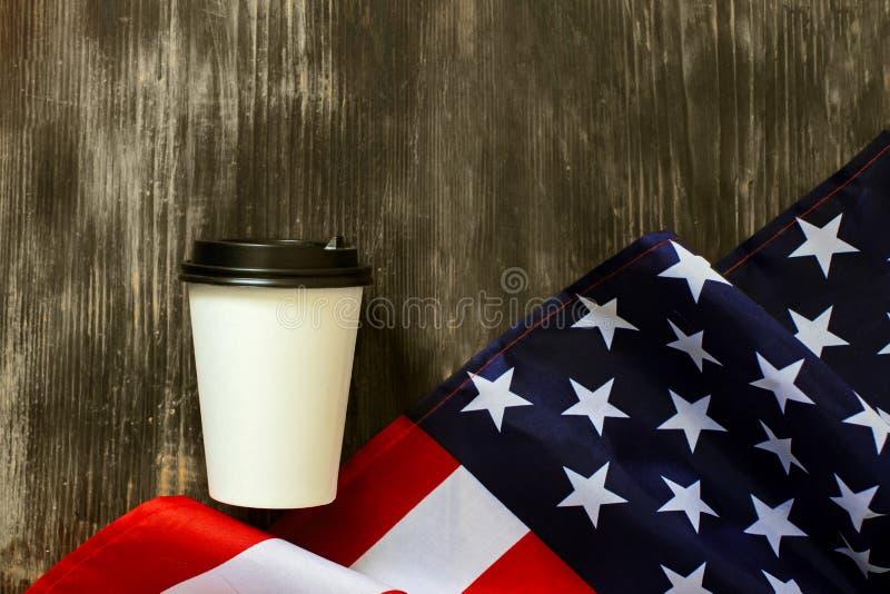 Papierschale der amerikanischen Flagge und des Kaffees auf einem alten hölzernen Hintergrund stockbild