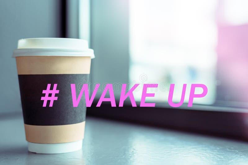 Papierschale des Getränks mit einer weißen Plastikkappe auf dem Fenster der Kaffeestube mit dem hashtag wachen, das Konzept eines lizenzfreies stockfoto