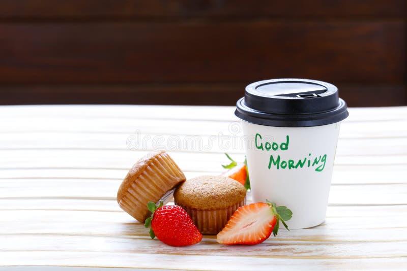 Papierschale mit heißem Kaffee und einem Muffin lizenzfreie stockbilder