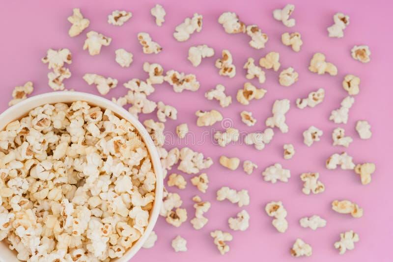 Papierschale mit Popcorn und dem Popcorn zerstreut auf einen rosa Pastellhintergrund, Draufsicht, copyspace stockfotografie