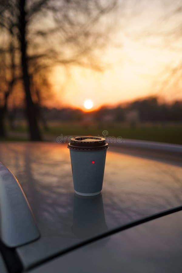 Papierschalenkaffee bei dem Sonnenuntergang, der auf einem Autodach mit sch?nem aus Fokus bokeh heraus steht stockfoto