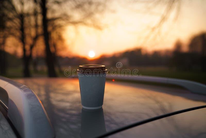 Papierschalenkaffee bei dem Sonnenuntergang, der auf einem Autodach mit sch?nem aus Fokus bokeh heraus steht lizenzfreies stockbild