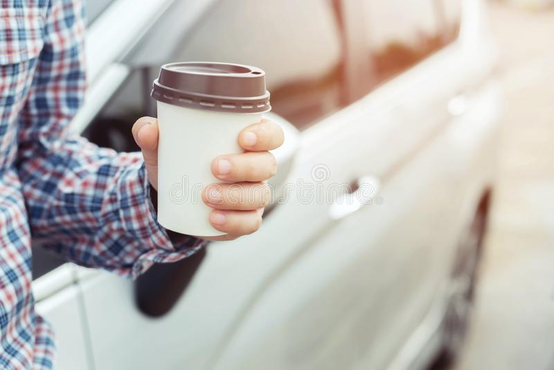 Papierschalenkaffee des Geschäftsmannes des geselligen Menschen trinkender von heißem in der Hand bei der Stellung des Autos auf  stockfotos