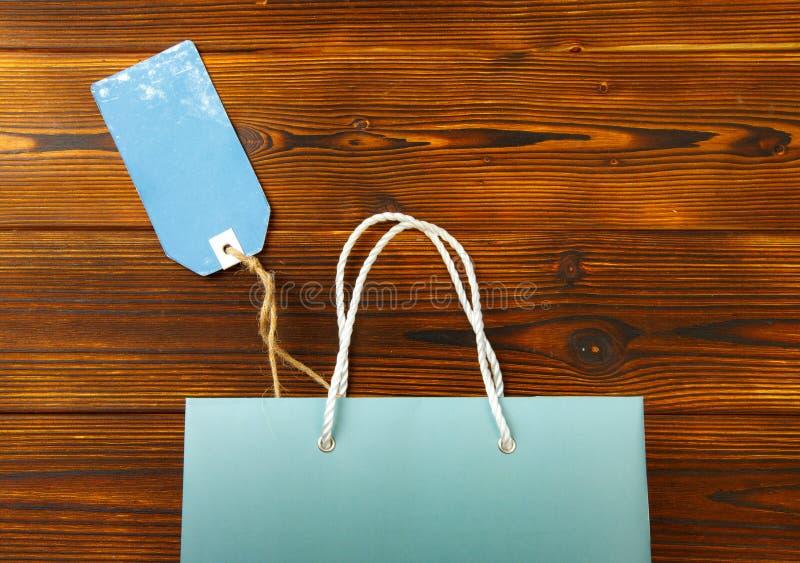 Papiertüte auf hölzernem Hintergrund mit Verkaufsumbau Modell f?r Design lizenzfreie stockfotos