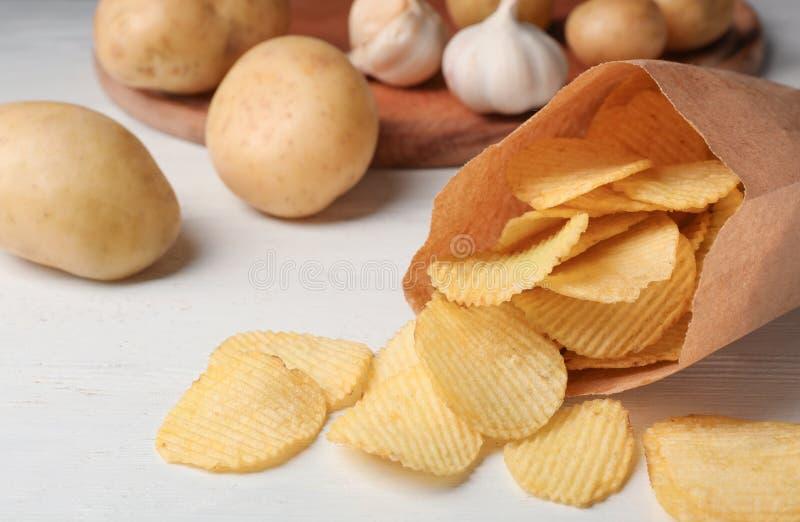 Papiert?te knusperige Kartoffelchips auf wei?em Holztisch lizenzfreie stockfotos