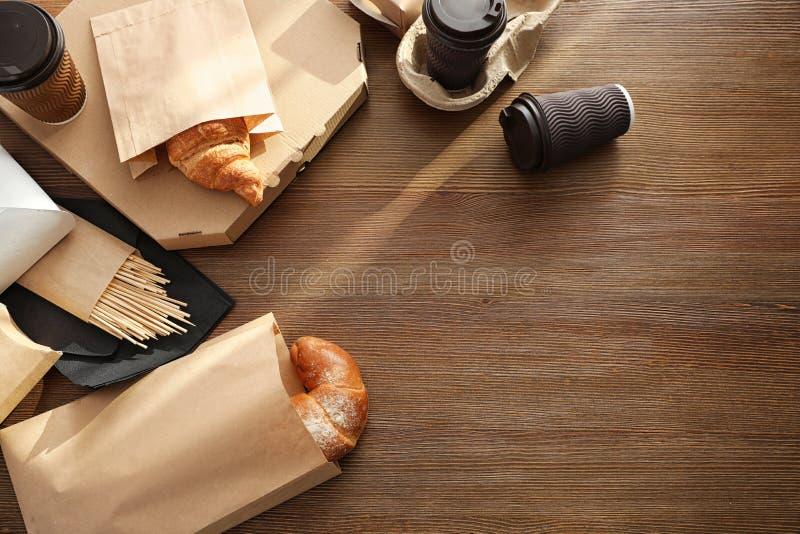 Papiertüten mit Gebäck und Mitnehmernahrung auf Holztisch, Draufsicht stockfoto