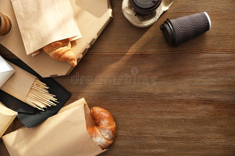 Papiertüten mit Gebäck und Mitnehmernahrung auf Holztisch, Draufsicht lizenzfreie stockfotos