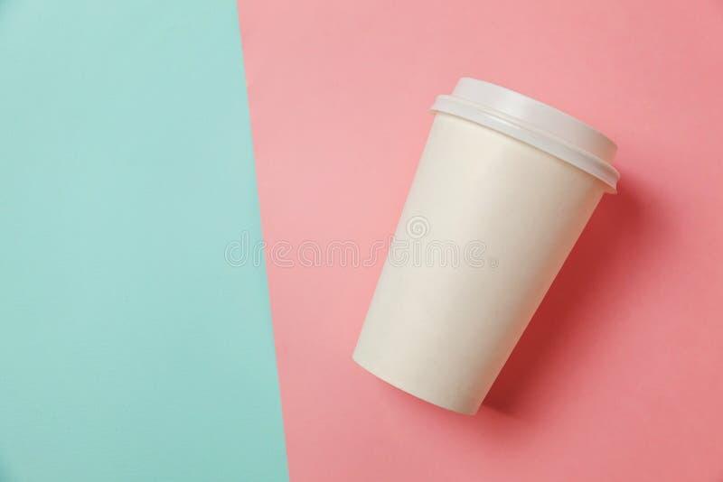 Papiertasse kaffee auf blauem und rosa Hintergrund lizenzfreie stockfotografie