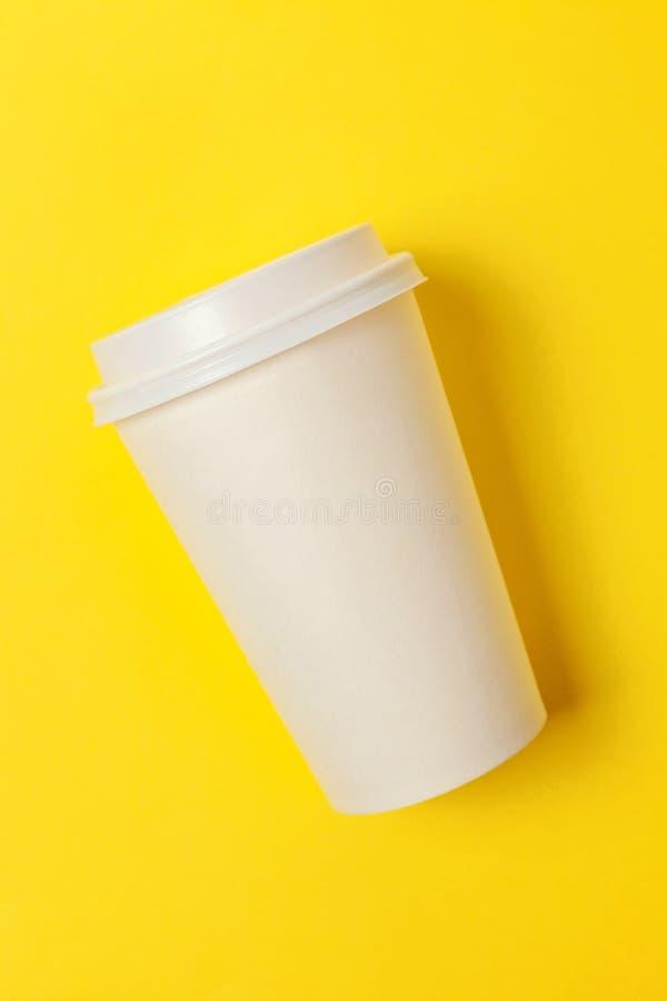 Papiertasse kaffee auf gelbem Hintergrund lizenzfreie stockbilder